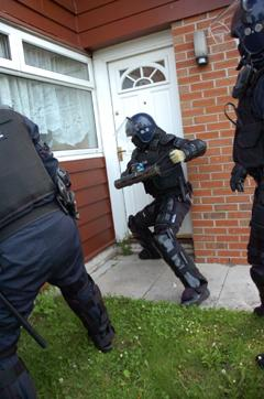 A POLICE officer forces his way into one of the homes.