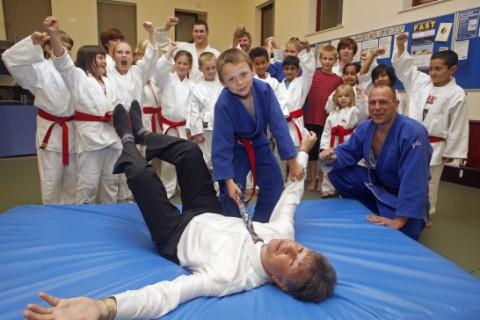 Graham Fenton, Co-operative's Cheshire Area Membership Committee, tries out the new mats at Crewe Judo Club that have been bought with cash from The Co-operative's Community Fund. Showing his skills is Logan Michaelson, watched by coach, Chris Sharpe