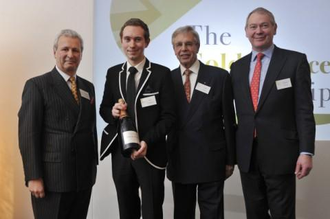 Ben Robinson holds a bottle of celebratory champagne alongside (l-r) chairman of the judges, Edward Griffiths, Gold Service Scholarship founder Willy Bauer and Alastair Storey, chairman of sponsors, BaxterStorey