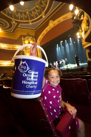 Mia, age six from Crewe, helps to fundraise for Great Ormond Street Hospital in the Lyceum Theatre's historic auditorium as theatre tours take place on stage in the background.